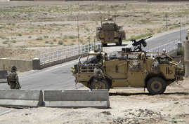 British troops keep watch at a checkpoint, where a man shot and killed three British soldiers, in Helmand province July 2, 2012. The man, an Afghan policeman, shot the soldiers at the checkpoint on Sunday, Afghan officials said, the latest in a chain