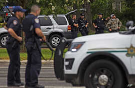 Law enforcement officers man a road block after police officers were shot earlier in the day in Baton Rouge, Louisiana, July 17, 2016. Multiple law enforcement officers were killed and wounded Sunday morning in a shooting near a gas station in Baton ...