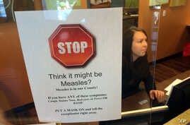 FILE - A sign warns of the dangers of measles in the reception area of a pediatrician's office in Scottsdale, Arizona, Saturday, Feb. 7, 2015.