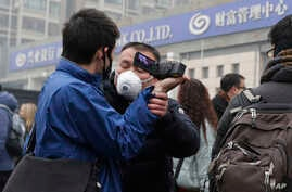 A plainclothes policeman grabs the hand of a foreign journalist as he prevents him from filming the supporters of rights lawyer Pu Zhiqiang's gathering near the Beijing Second Intermediate People's Court in Beijing, Dec. 14, 2015.