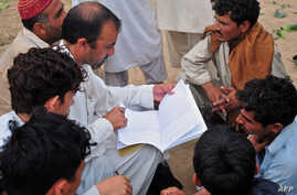 Naim ullah Khattak (L), an Election Commission of Pakistan (ECP) worker, verifies voters using a list from the Computerized National Identity Card (CNIC) database in the outskirts of Islamabad on Sept. 12, 2011.
