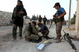 Rebel fighters are seen tending to their weapons, in Aleppo, Syria, August 6, 2016.