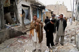 Onlookers stand over the site of a bomb blast outside a Shiite Muslim mosque in Hangu, February 1, 2013.