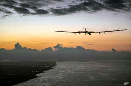 FILE - In this photo provided by Jean Revillard, Solar Impulse 2, a plane powered by the sun's rays and piloted by Andre Borschberg, approaches Kalaeloa Airport near Honolulu, July 3, 2015.