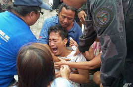 A survivor of a passenger ferry that capsized in rough waters cries after arriving at the pier in Ormoc City, central Philippines, July 2, 2015.