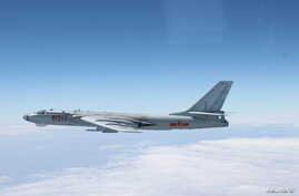 A Chinese military plane H-6 bomber flies through airspace between Okinawa prefecture's main island and the smaller Miyako island in southern Japan, out over the Pacific, in this handout photo taken October 27, 2013 by Japan Air Self-Defence Force an...
