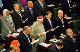Tunisian parliament members take their oath of office on the Quran during the inaugural session of the newly elected Tunisian parliament in Tunis, Dec. 2, 2014.
