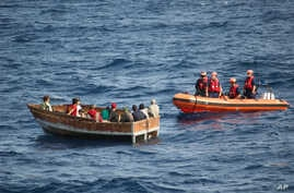 Members of the U.S. Coast Guard Cutter Knight Island approach a boat with 12 Cuban migrants southwest of Key West, Florida, Dec. 30, 2014.