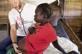 MSF HIV specialist Dr. Eamonn Vitt examines an HIV positive Ugandan woman who's 7 months pregnant. (Nov. 2009)