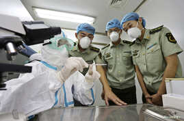A health inspection and quarantine researcher (L) demonstrates to customs policemen the symptoms of Ebola, at a laboratory at an airport in Qingdao, Shandong province, Aug. 11, 2014.