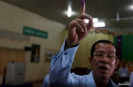 Cambodia's Prime Minister and President of the Cambodian People's Party , Hun Sen shows his ink-stained finger during a Senate election in Takhmao, Kandal province, Cambodia, Feb. 25, 2018.