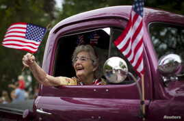 A woman waves an American flag as she rides in an antique pickup truck through Barnstable Village on Massachusetts' Cape Cod during the community's annual Independence Day parade, July 4, 2015.