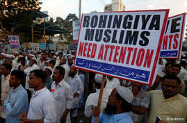 A Human Rights Network activist holds a sign during a demonstration against the persecution of Rohingiya Muslims in Myanmar, in Karachi, Pakistan Dec. 9, 2016.