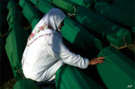 A woman touches the coffin of her relative among the over 600 displayed at the Potocari memorial cemetery near Srebrenica, some 160 kilometers east of Sarajevo, Bosnia-Herzegovina,  July 11, 2011