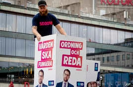 """Election posters of the Sweden Democrats are put up by a party member in Stockholm, Aug. 30, 2018. The poster for the Sept. 9, 2018, election reads, """"Welfare must work"""" and """"Law and order."""""""