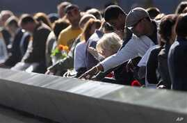 Family members view the names of their relatives etched into the 9/11 Memorial during the commemoration of the 11th anniversary of the terrorist attacks on the World Trade Center in New York, September 11, 2012.