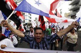 A demonstrator carries a Panamanian flag during a 'Cumbre de los Pueblos' or 'People's Summit' protest against U.S. policies in Latin America, in Panama City, April 9, 2015. Panama hosts the Summit of the Americas April 10-11.