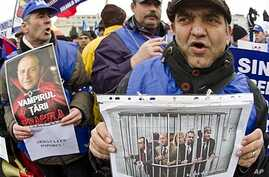 Protesters hold manipulated pictures of government leaders, Bucharest, Jan. 24, 2012.