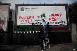 "Young members of Britain's opposition Labor Party write on a billboard why they want Jeremy Corbyn, the party leader, to back a ""People's Vote"" second referendum on Britain's European Union membership, during a publicity stunt in Islington North, Cor"