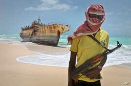 FILE - masked and armed Somali pirate Hassan stands near a Taiwanese fishing vessel washed ashore after the pirates were paid a ransom and the crew were released.