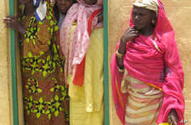 Women peer out of a doorway at the Kwali rehabilitation ce