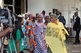 Some of the 21 Chibok schoolgirls released by Boko Haram follow Minster of Women Affairs Aisha Alhassan after their visit to meet President Muhammadu Buhari In Abuja, Nigeria Oct. 19, 2016