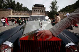 FILE - A man places his hand near the logo of a Rolls Royce at the Shuiguan Great Wall on the outskirts of Beijing, China, Sept. 18, 2011. A new law now tries to coordinate charitable giving by country's richest.