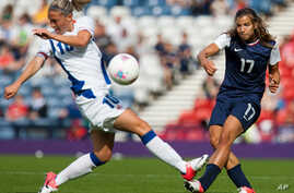 France's Camille Abily, left, attempts to stop a shot by United States' Tobin Heath during the women's group G soccer match between the United States and France prior to the start of the London 2012 Summer Olympics at Hampden Park Stadium in Glasgow,