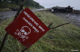FILE - A destroyed military vehicle is seen near a landmine warning sign just outside the eastern Ukrainian town of Slaviansk, July 7, 2014.