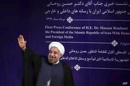 Iran's new President Hasan Rouhani waves to reporters at the conclusion of his first press conference since taking office at the presidency compound in Tehran, Aug. 6, 2013.
