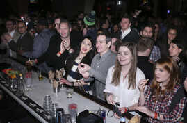 "FILE - Guests gather to watch the Super Bowl, Feb. 2, 2014, in New York. During flu season, ""Anytime that you have large groups of people congregating in enclosed spaces you know it always offers an opportunity for more efficient spread of germs,"" an"
