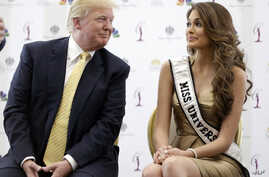 FILE - Donald Trump (L) and 2014 Miss Universe, Gabriela Isler, of Venezuela, talk during a news conference Oct. 2, 2014, in  in Doral, Florida.