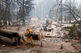 A firefighter extinguishes a hot spot in a neighborhood destroyed by the Camp Fire in Paradise, California, Nov. 13, 2018.