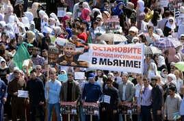 "RuChechens hold a banner reading ""Stop genocide of Muslims in Myanmar"" during a mass protest in Chechnya's provincial capital Grozny, Sept. 4, 2017."