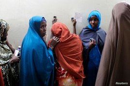 Leyla Ali Adow (C), a suspected Somali illegal migrant arrested in a police swoop reacts after being processed for deportation at a holding station in Kenya's capital Nairobi, April 9, 2014.