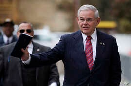 U.S. Sen. Bob Menendez waves at reporters before entering the Martin Luther King Jr. Federal Courthouse for his federal corruption trial, Nov. 16, 2017, in Newark, N.J.