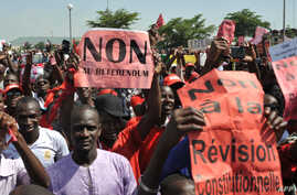 """FILE - Protestors carry a sign reading """"No to the referendum"""" and """"No to Constitutional revision"""" during a demonstration against a referendum on a constitutional revision on July 1, 2017, in Bamako."""