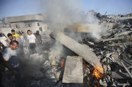 People gather as a Palestinian man reacts next to the rubble of his house, which witnesses said was destroyed in an Israeli air strike, in Rafah in the southern Gaza Strip Aug. 20, 2014.