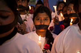 FILE - Indian women participate in a candle light vigil at a bus stop where the victim of a 2012 deadly gang rape had boarded the bus on what would become her final journey, in New Delhi, India, Dec. 16, 2014.
