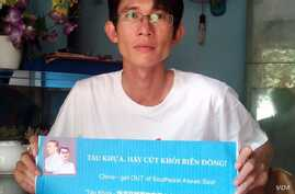 Before his arrest, Vietnamese blogger Dinh Nhat Uy holds a sign protesting China's territorial claims in the South China Sea.