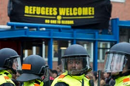 """FILE - Two demonstrators carry a banner reading """"Refugees Welcome"""" as Dutch riot police separates them from an anti-islam Pegida demonstration in Amsterdam, Netherlands, Saturday, Feb. 6, 2016."""