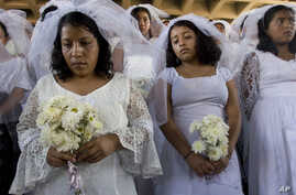 FILE - Women dressed as brides protest in commemoration of the international day for the elimination of violence against women, outside the Supreme Court in Guatemala City, Nov. 26, 2007.