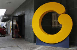 FILE - An employee walks through a door at the headquarters of Venezuelan TV channel Globovision, in Caracas, Venezuela, March 12, 2013.
