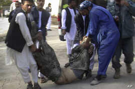 Afghans carry the body of a suicide attack victim at the hospital in Maymana, Faryab province northwest of Kabul, Afghanistan, October 26, 2012.
