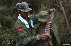 FILE - A rebel soldier of Myanmar National Democratic Alliance Army (MNDAA) places a machine gun bullet belt around the neck of another soldier at a military base in Kokang region, March 10, 2015.