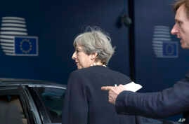 British Prime Minister Theresa May, left, is guided to her car as she leaves an EU summit at the Europa building in Brussels, Belgium, June 22, 2017.