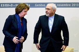 EU foreign policy chief Catherine Ashton (L) and Iranian Foreign Minister Mohammad Javad Zarif rise after a photo opportunity ahead of closed-door nuclear talks at the United Nations European headquarters in Geneva, Switzerland. Nov. 20, 2013.