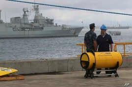 A U.S. naval officer talks with a crewman as they stand next to part of the towed pinger locator before its fitted to the defense ship Ocean Shield to aid in her roll in the search for missing Malaysia Airlines Flight MH370 in Perth, Australia, Sunda