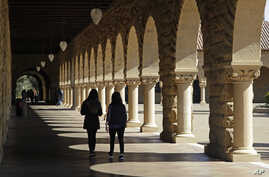 FILE - Students walk on the Stanford University campus, March 14, 2019, in Santa Clara, Calif.