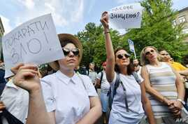 FILE - An activist holds a placard reading 'Punish evil!' (L) during a protest in front of the Ukrainian Ministry of Internal Affairs in Kiev on August 1, 2018, a day after a shocking acid attack on civil activist Kateryna Gandzyuk.